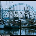 Commercial fishing boats and Yaquina Bay Bridge at dawn. Newport, Oregon, USA